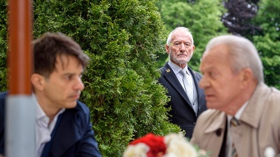 Alfons (Sepp Schauer, M.) steht im Hintergrund; Robert (Lorenzo Patané, l.) und Werner (Dirk Galuba, r.) sitzen an einem -Tisch.
