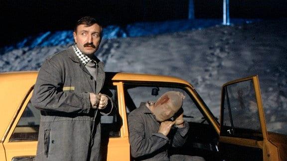 """Kellner Horst Frischmuth (Michael Narloch, li.) steht neben einem PkW """" Lada"""";  sein Freund Peter Lommer (Günter Schubert) sitzt im PkW mit geöffneter rechter Tür. Er streift sich eine Maske über."""
