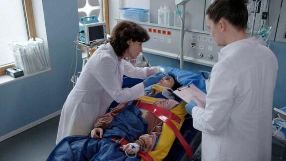 Sina Kilic (Zeynep Bozbay, M.) kommt nach einem Verkehrsunfall ins Klinikum. Karin Patzelt (Marijam Agischewa, l.) und Tom Zondek (Tilman Pörzgen, r.) versuchen das zerschmetterte Bein zu retten.