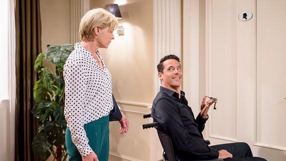 Linda (Julia Grimpe, l.)  steht hinter Dirk (Markus Pfeiffer, r.), der im Rollstuhl sitzt.