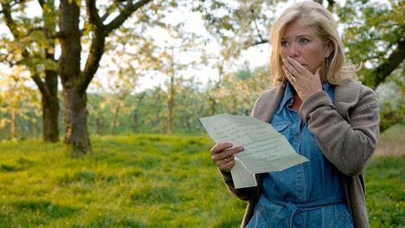 Anna (Jutta Speidel) hält einen Brief von ihrer Tochter in den Händen. Sie fasst sich erschrocken an den Kopf.