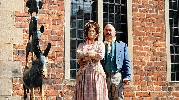 Die Schauspieler Anna Fischer und Johannes Zirner in historizierenden Kostümen vor den odem Denkmal der Bremer Stadtmusikanten am Rathaus.