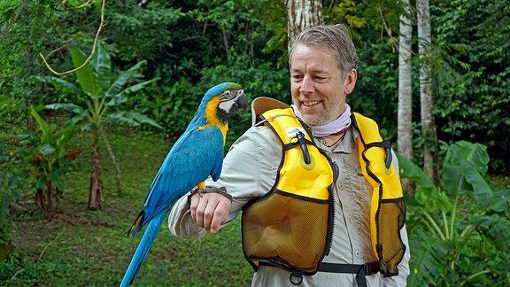 Biwak-Moderator Thorsten Kutschke im Madidi Nationalpark mit einem Ara