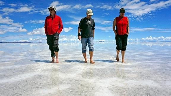 Spaziergang dreier Wanderer auf dem Salz - Salar de Uyuni