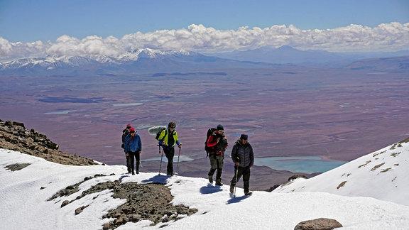 Aufstieg zum Uturuncu 6008 m - Cordillera de Lípez. Vier Bergsteiger schreiten über abgerundete Felsen, mit Schee leicht bedeckt.