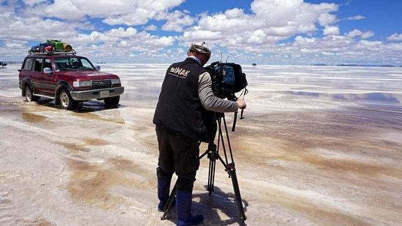 Gelängegängiger PkW fährt auf dem größten Salzsee der Welt - Salar de Uyuni. Ein Kameramann im Vordergrund nimmt das auf.