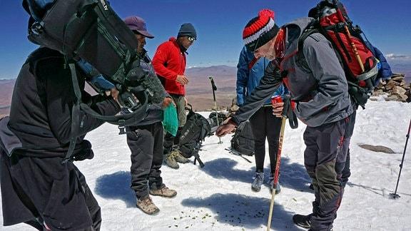Traditionelle Gipfelzeremonie mit Kokablättern auf dem Uturuncu 6.008 m .  Der Gipfel ist abgerundet und leicht mit Schnee bedeckt.