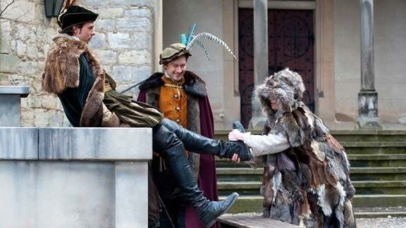 Allerleirauh (Henriette Confurius) zieht Jakob (André Kaczmarczyk) die Stiefel aus, Rasmus (Adrian Topol) sieht zu.