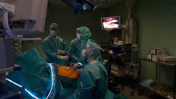 Die Chirurgen bei der Arbeit im abgedunkelten OP-Saal