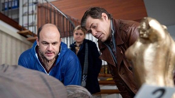 Der Pathologe Dr. Strahl (Christoph Tomanek, l.)  und Finn Kiesewetter (Sven Martinek , r.) betrachten eine am Boden liegende Person. Sandra Schwartenbeck (Marie-Luise Schramm, M.) beobachtet sie.