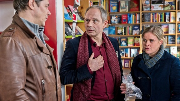 Sandra Schwartenbeck (Marie-Luise Schramm, r.) und Finn Kiesewetter (Sven Martinek , l.) sprechen mit dem Tatverdächtigen Didier Moretti (Michael Lott, M.),vor einer bunten Glaswand.