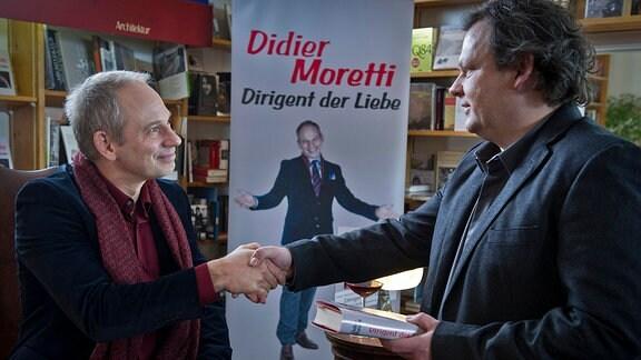 """Der Lübecker Autor des Bestsellers """"Dirigent der Liebe"""" Didier Moretti (Michael Lott, l.) gibt dem  Drucker Malte Henning (Ulrich Bähnk, r. die Hand."""