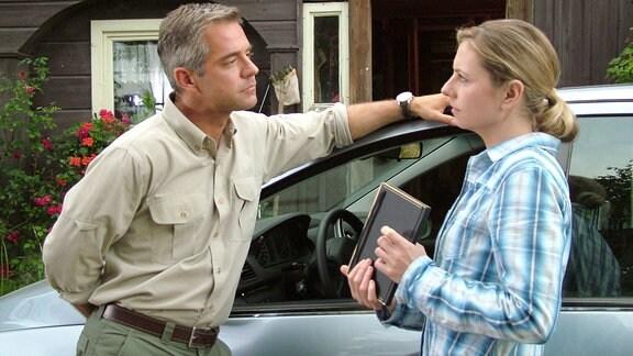 Mark (Florian Fitz) und Claudia Schmitt (Susanne Michel). stehen sich vor einem PkW und einem Umgebindehaus gegenüber.
