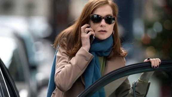 Michèle  (mit Sonnenbrille) telefoniert.