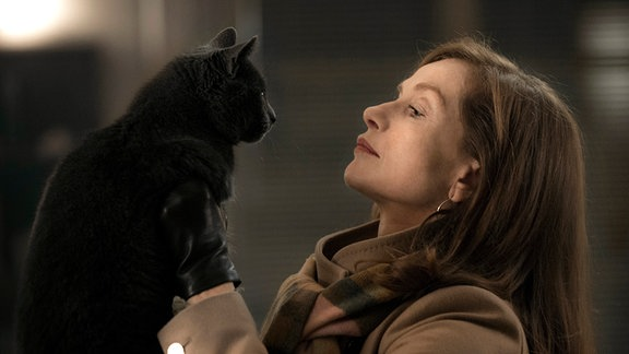 Michèle Leblanc (Isabelle Huppert) - im Profil - hält eine schwarze Katze vor ihrer Brust.