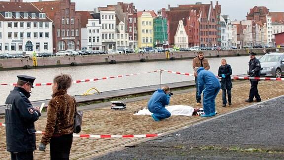 Im Lübecker Industriegebiet am Hafen wird die Leiche des Schauspielers Roland Freesmann gefunden. Die Ermittler Finn Kiesewetter (Sven Martinek, 3.v.r.) und Sandra Schwartenbeck (Marie-Luise Schramm, 2.v.r.) machen sich vor Ort ein Bild vom Tatort. (weitere Personen: Komparsen)