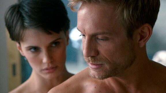 Eine nackte Frau steht hinter einem nackten Mann.