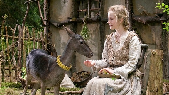 Odine Johne als Schwesterchen mit Reh vor einer Hütte.