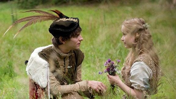 Der König (Jonas Jägermeyr) blickt Schwesterchen (Odine Johne) auf einer Wiese in die Augen.