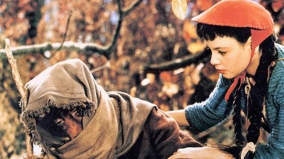 Rotkäppchen (Blanche Kommerell) berührt den Wolf. Dieser (Werner Dissel) verhüllt mit einem Kopftuch seinen Kopf.