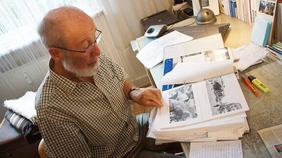 Der Ingenieur Reiner Halle blättert in einem Ordner mit Fotos.