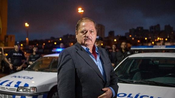 Eduardo Silva (Jürgen Tarrach) vor Polzeifahrzeugen; das nächtliche Lissabon im Hintergrund,
