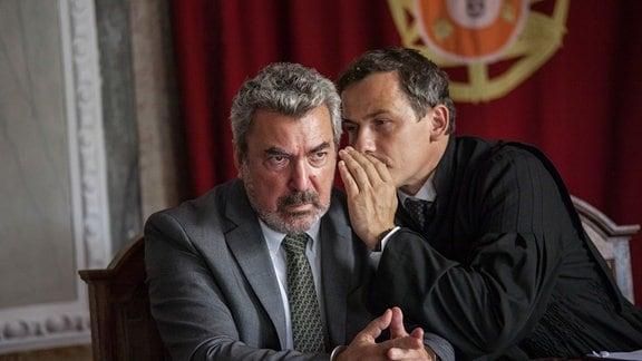 Tiago Zarco (André Gago)wird von seinem Anwalt Abel Ferreira (Ben Bela Böhm) etwas zugeflüstert; Zarco blickt mürrisch.