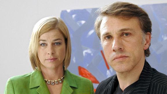 Das Ehepaar Sybille und Robert Henze (Ingrid Sattes und Christoph Waltz) werden von Hauptkommissar Ehrlicher über den Tod von Gabriele Teichert informiert.