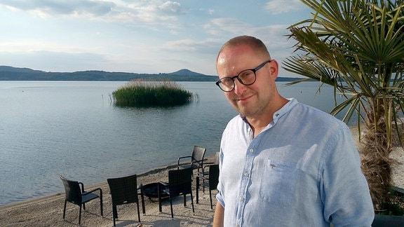 Conrad Schroepel vor einem See mit Strand, auf denen ein paar Gartenmöbel stehen.