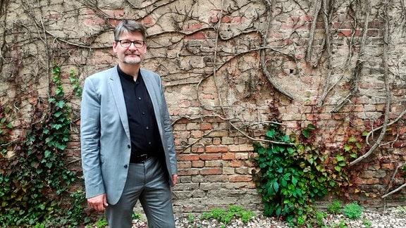 Matthias Lerm vom Stadtplanungsamt Magdeburg steht vor einer vertrockneten Fassadenbegrünung.