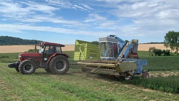 Ein Traktor und ein Mähdrescher auf einem grünen Feld.