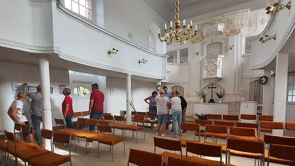 Das Innere der Kirche - weiß gestrichen, mit goldenen Kronleuchtern verziert und braunen Stühlen ausgestattet.