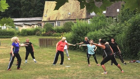 Eine Gruppe Frauen in Sportkleidung deht sich in einem Garten.