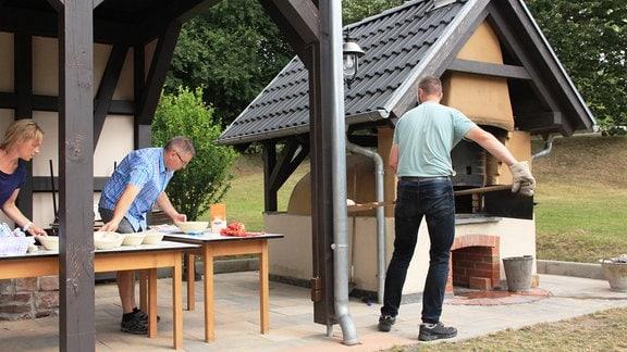 Zwei Personen bereiten Teig auf einer Fachwerkterasse, während eine dritte Person Teig in einen historischen Lehmbackofen schiebt.