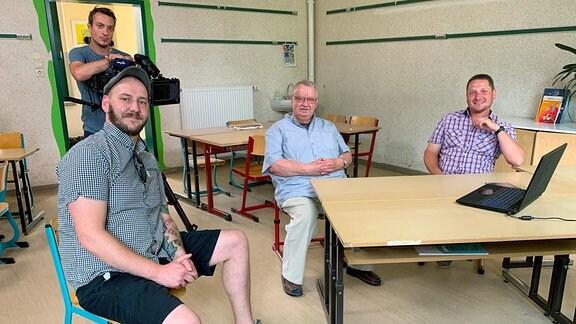 Hartmut Bock (Mitte), früher Geschichtslehrer und heute Heimatforscher in seinem Heimatort Jübar, mit seinen ehemaligen Schülern Manuel Härting (li.) und Michael Neumann (re.) in der Schule von Jübar.