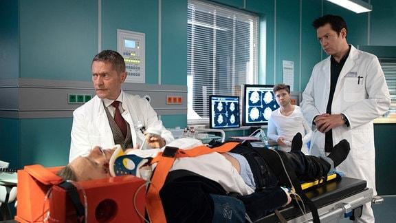 Hauke Friedrich (Oliver Konietzny, liegend) ist schwer aufs Becken gestürzt und Dr. Brentano (Thomas Koch, re.) zieht Dr. Kaminski (Udo Schenk, li.) zu Rate. Dieser bittet Kris Haas (Jascha Rust, 2.v.re.) ein Kontrastmittel-CT vorzubereiten.