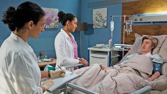 Hannes Dorn (Alessandro Schuster, rechts, im Bett liegend) hatte eine unschöne Begegnung mit einer Stichsäge. Nach der OP untersuchen ihn die beiden Ärztinnen Leyla Sherbaz (Sanam Afrashteh, l.) und Emma Jahn (Elisa Agbaglah, Mitte, beide stehend).