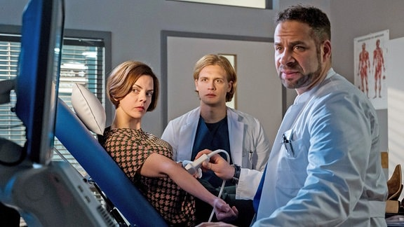 Während der Untersuchung von Ramona Zergiebel (Camilla Renschke, l.) wetteifern die beiden Ärzte Mikko Rantala (Luan Gummich, M.) und Matteo Moreau (Mike Adler, r.)