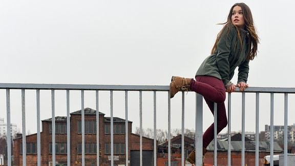 Jenny (Zoe Moore) klettert über ein Geländer.