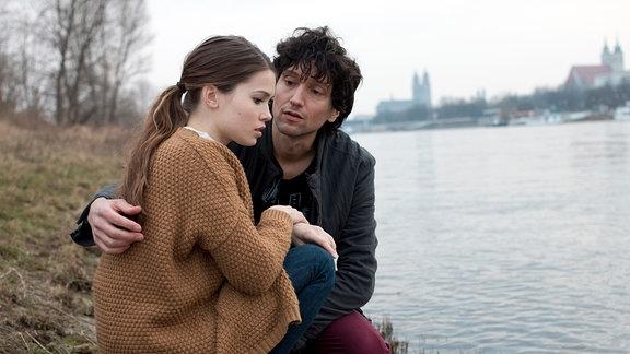 Jenny (Zoe Moore, links) und Kai (Thomas Fränzel, rechts) sitzen am Strand eines Gewässers.