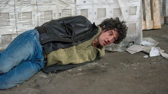 Kai Förster (Thomas Fränzel) liegt gefesselt auf einem Betonboden. Hinter ihm eine Pallette mit eingeschweißten Fliesen.
