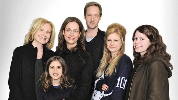 Die erfolgreiche Marketingspezialistin Fiona (Claudia Michelsen, 2. v. links) hat gemeinsam mit ihren beiden Töchtern Paulette (Luise Aschenbrenner, rechts) und Lina (Laura Kirsch, unten links), ihrer Mutter Gitta (Maren Kroymann, links) sowie ihrem Mann Ben (Stephan Kampwirth) und dessen Geliebter Julia (Birte Hanusrichter) eine etwas andere Familie gegründet.