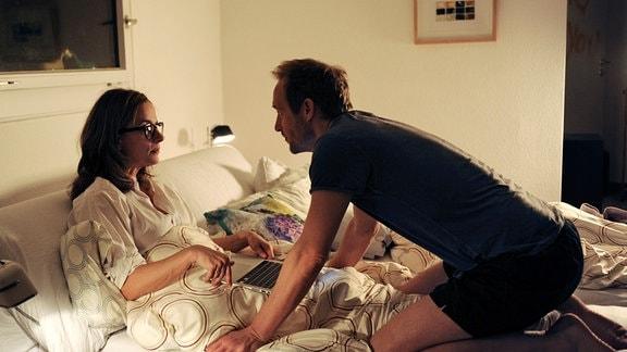 Ben (Stephan Kampwirth) kniet im Bett vor Frau Fiona (Claudia Michelsen).