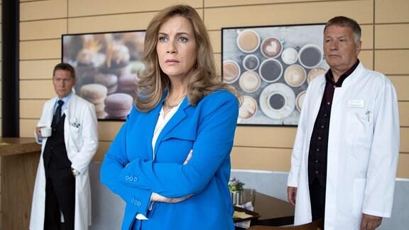 Sarah Marquardt ist gerade im Gespräch mit Dr. Heilmann und Dr. Kaminski, als sie feststellt, dass sie von der anderen Straßenseite von Tobias Rauch beobachtet wird. Doch die beiden Ärzte sehen niemanden.
