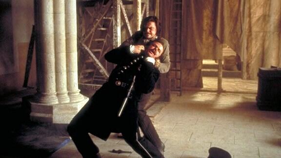 """Amsterdam Vallon (Leonardo DiCaprio) knöpft sich den korrupten Polizisten """"Happy Jack"""" Mulraney (John C. Reilly, vorne) vor."""
