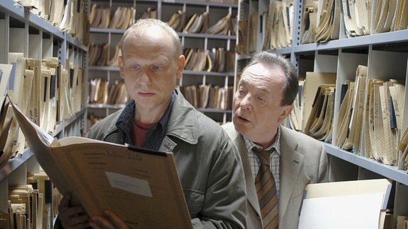 Hauptkommissar Kain (Bernd Michael Lade, links) und Hauptkommissar Ehrlicher (Peter Sodann, rechts) halten Akten in den Händen.