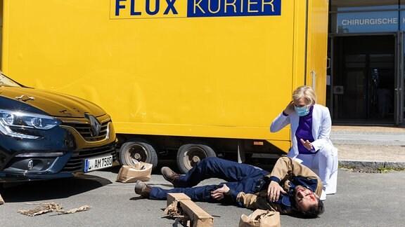 Dr. Kathrin Globisch (Andrea Kathrin Loewig) hat gerade ein Paket übergeben bekommen, als der Bote (Hadi Khanjanpour) direkt vor der Sachsenklinik von einem Auto angefahren wird.