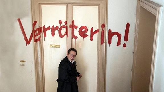 """Hans (Uwe Kockisch, l.) eilt besorgt zu Dunja - über ihrer Tür wurde in roten Lettern """"Verräterin !"""" geschrieben."""
