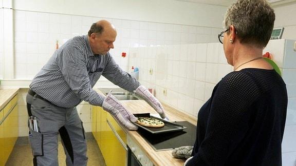 Mit Hilfe von Rehabilitationstrainerin Sabine Scheffler lernt der blinde Rainer eine Ofenpizza zu backen.