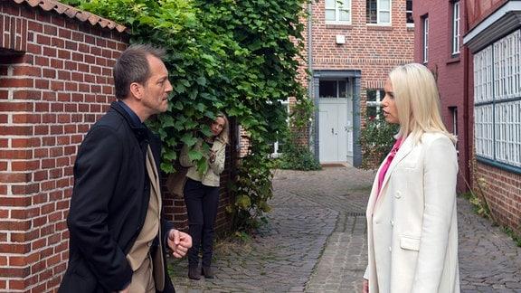 Monas (Jana Hora-Goosmann, h.) Eifersucht wird geschürt, als sie Andreas (Herbert Schäfer, l.) zusammen mit Amelie (Lara-Isabelle Rentinck, r.) sieht.